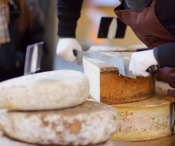 Seller cutting organic cheese on farmer market in Strasbourg, France. Typical European local farmer market. Organic food.