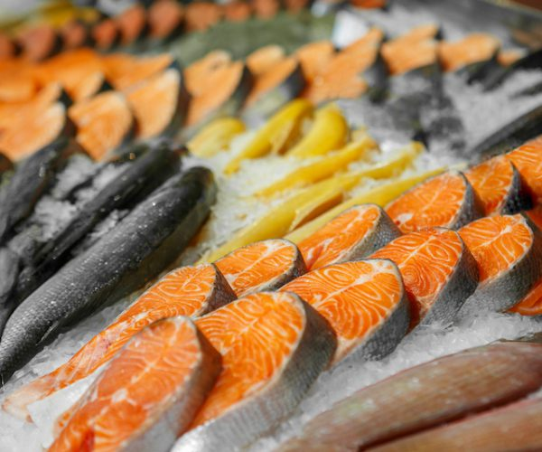 Close up of cooled seafood - trout, sockeye, sea bass, in the market of a fish shop, supermarket, horizontal frame, side view